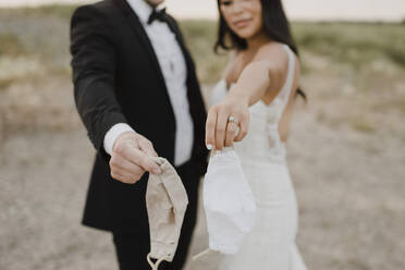 Bride with groom showing protective face mask in field during COVID-19 - SMSF00273