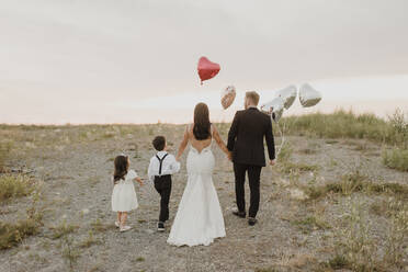 Parents and children wearing wedding dress while walking with heart shape balloons in field against sky - SMSF00276