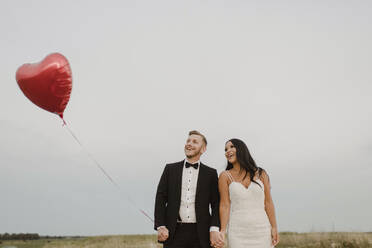 Happy bride and groom with heart shape balloon against sky - SMSF00288