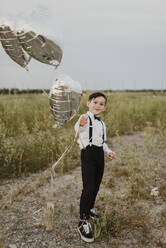 Boy with heart shape balloons standing in field against clear sky - SMSF00291
