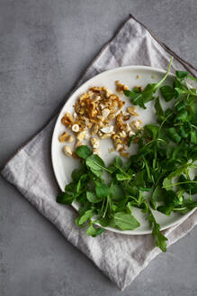 From above plate with assorted nuts and fresh herbs placed on napkin during baked sweet potato salad preparation - ADSF13018