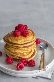 Stack of tasty pancakes with ripe raspberries placed on plate near spoons on gray background - ADSF13097