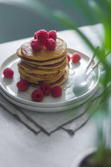 From above plate of delicious pancakes with raspberries placed on napkin near potted plant in morning - ADSF13100