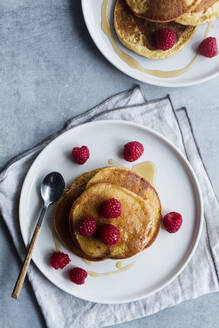From above top view of tack of tasty pancakes with ripe raspberries placed on plate near spoons on gray background - ADSF13103