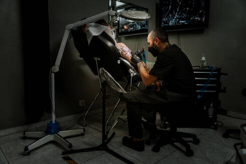 Side view of male with face mask master tattooing unrecognizable client lying in chair near floor lamp in tattoo parlor while using tattoo machine - ADSF13339