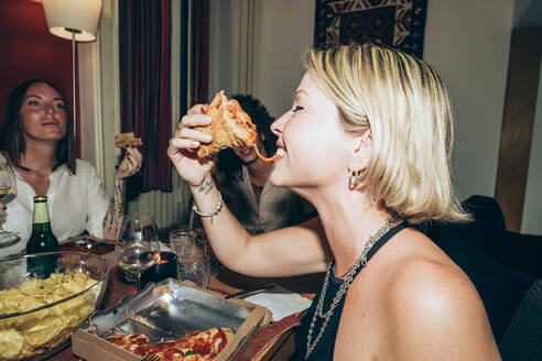 Smiling young woman eating pizza during party - MEUF01983