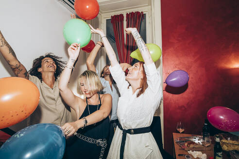 Male and female friends dancing with colorful balloons during party - MEUF02001