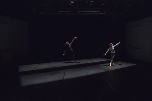 Male and female dancer performing comtemporary ballet on black stage - NGF00607