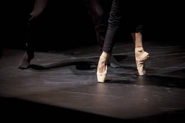 Close up of dancers dancing en pointe on black stage - NGF00610