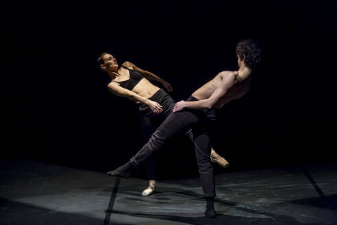 Male and femal dancer performing contemporary ballet on black stage - NGF00619