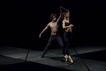 Male and femal dancer performing contemporary ballet on black stage - NGF00622