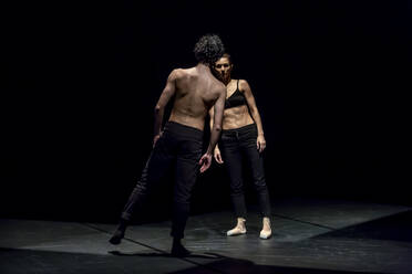 Male and femal dancer performing contemporary ballet on black stage - NGF00628