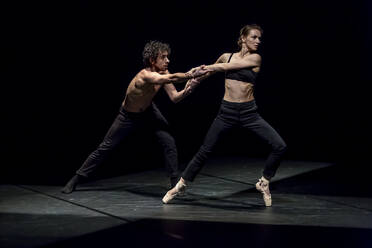 Male and femal dancer performing contemporary ballet on black stage - NGF00631