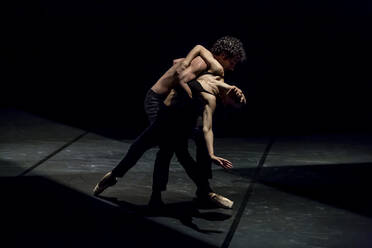 Male and femal dancer performing contemporary ballet on black stage - NGF00634