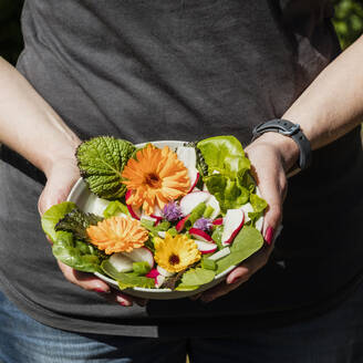 Close-up of woman holding plate with lettuce and edible flowers - EVGF03735