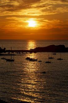 France, Haute-Corse, LIle-Rousse, Silhouettes of sailboats in front of small Mediterranean island at moody sunset - UMF01001