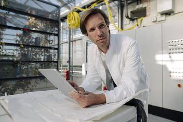 Scientist holding tablet in technical room of a greenhouse - JOSEF01612
