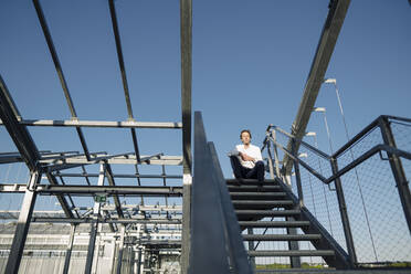 Scientist sitting on stairs under blue sky - JOSEF01624