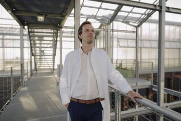 Confident scientist standing on a bridge - JOSEF01627