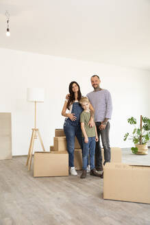 Happy family standing by cardboard boxes against wall in new home - MJFKF00549