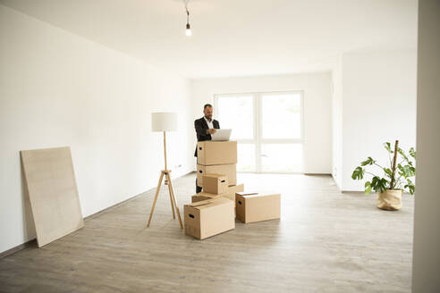 Businessman working over laptop on stacked boxes while standing in new apartment - MJFKF00588
