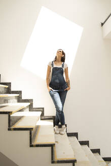 Pregnant woman with hands in pockets standing on steps against wall in new house - MJFKF00603