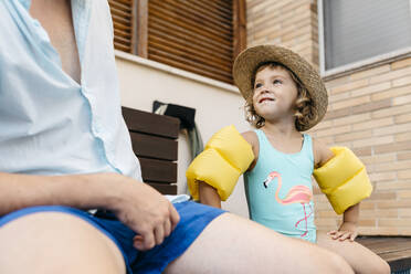 Little girl with her uncle sitting on poolside - JRFF04694