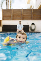 Little girl in swimming pool, her uncle on poolside - JRFF04697