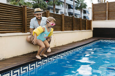 Little girl jumping into water, her uncle at poolside - JRFF04700