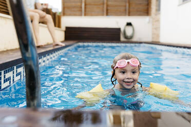 Little girl with swimming goggles in swimming pool - JRFF04706