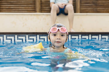 Little girl with swimming goggles in swimming pool - JRFF04709