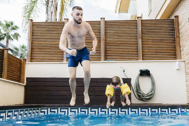 Little girl jumping with uncle into swimming pool - JRFF04712