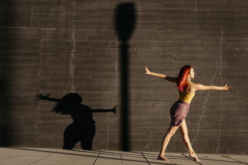 Dancing young woman casting shade on black wall at sunset - TCEF00989