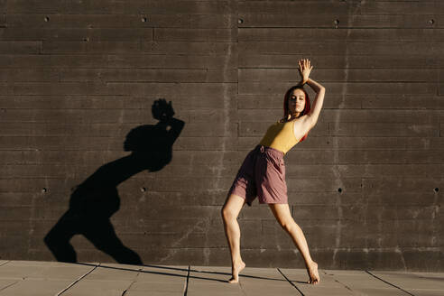 Dancing young woman casting shade on black wall at sunset - TCEF00992