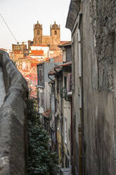 Portugal, Porto District, Porto, Alley stretching along old townhouses with Porto Cathedral in background - NGF00652