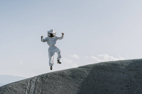 Man wearing a beekeeper dress jumping on a hill - AFVF07076