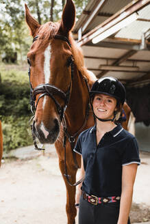 Delighted female equestrian in uniform standing with chestnut horse before dressage and looking at camera - ADSF13962
