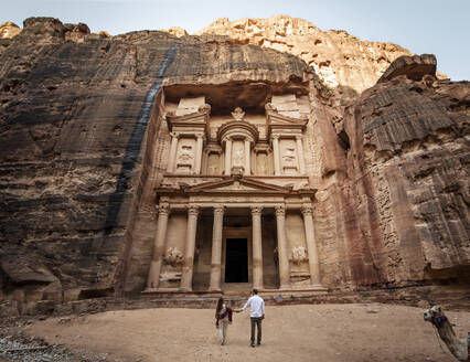 Back view of loving couple of tourists hugging and admiring view old ornamental facade of Al Khazneh temple in Jordan - ADSF14117