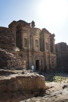 Back view of unrecognizable tourist standing admiring view old ornamental facade of Al Khazneh temple in Jordan - ADSF14123