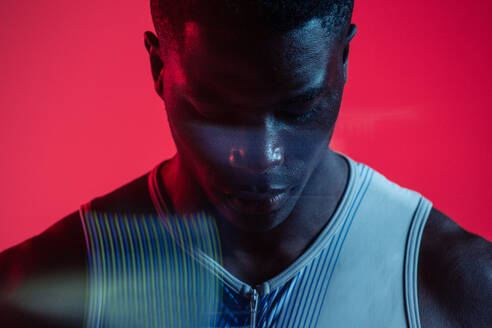 Professional young African American sportsman in sportive outfit standing in studio with red neon illumination with eyes closed - ADSF14150