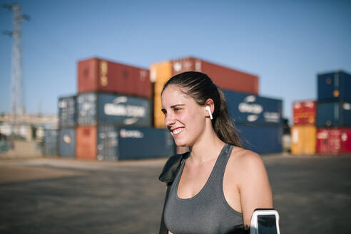 Portrait of smiling athletic woman with earphone and arm pocket for smartphone in industrial park - GRCF00356