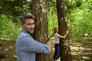 Man and woman hugging tree while standing in forest - ECPF01032