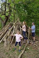 Happy family building camp with log in forest - ECPF01050