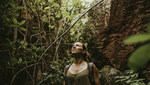 Woman trekking in forest between rock and trees - DMGF00122