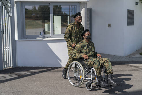 Army soldier helping military officer while pushing wheelchair - MTBF00643