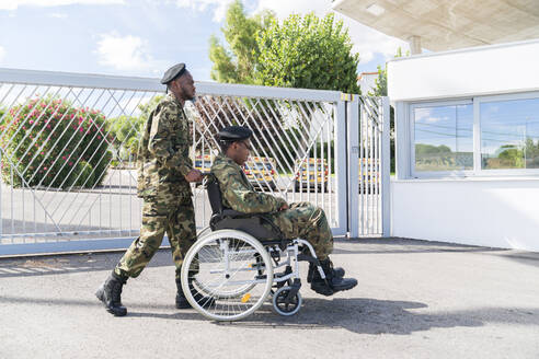 Army soldier helping military soldier on wheelchair while standing against gate on sunny day - MTBF00649