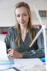 Woman at desk in office looking at wind turbine model - FKF03839