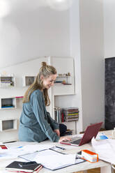 Smiling woman using laptop on desk in home office - FKF03842