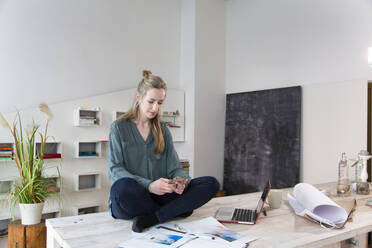 Woman sitting on desk in home office using smartphone - FKF03848