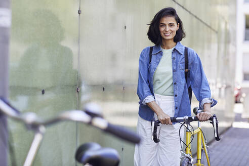 Smiling businesswoman with bicycle standing by wall in city - MCF01267